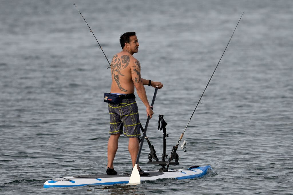 fishingman paddling on a SUP with fishing poles attached