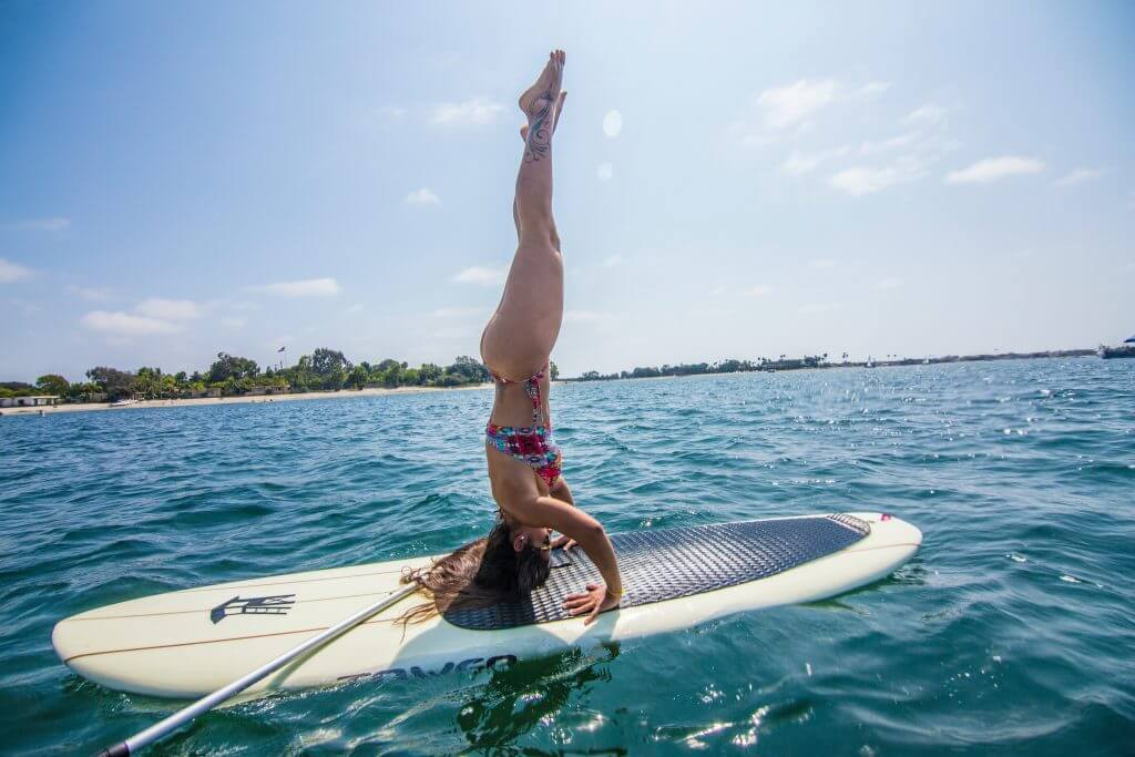 woman handstand yoga pose on a sup