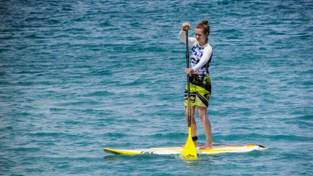 girl on SUP with a yellow paddle