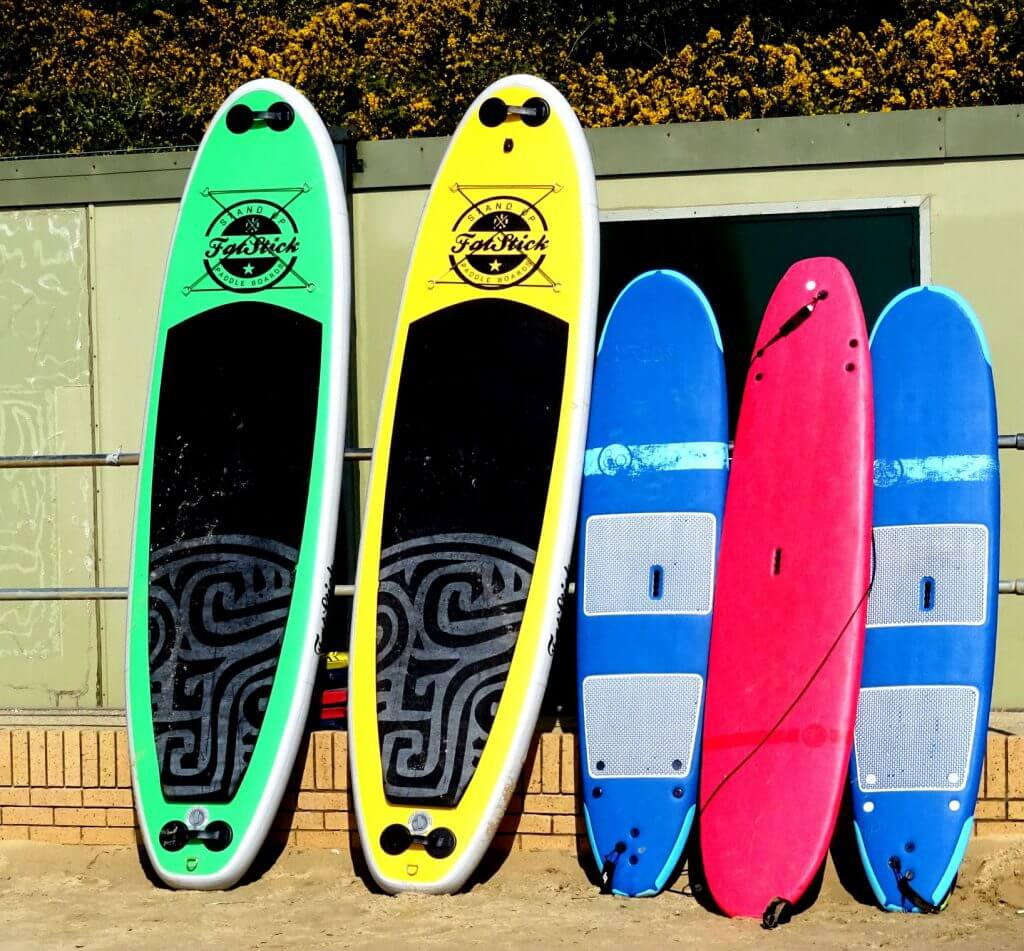 5 stand up paddleboards leaning against a wall