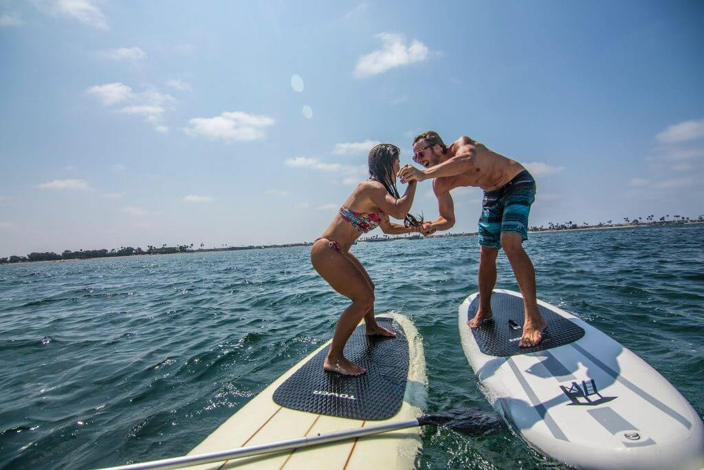a couple wrestling on SUP's