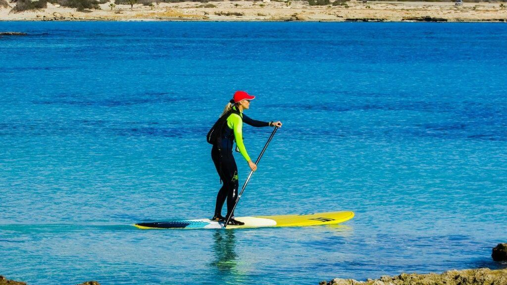 women on a stand up paddleboard with a red hat