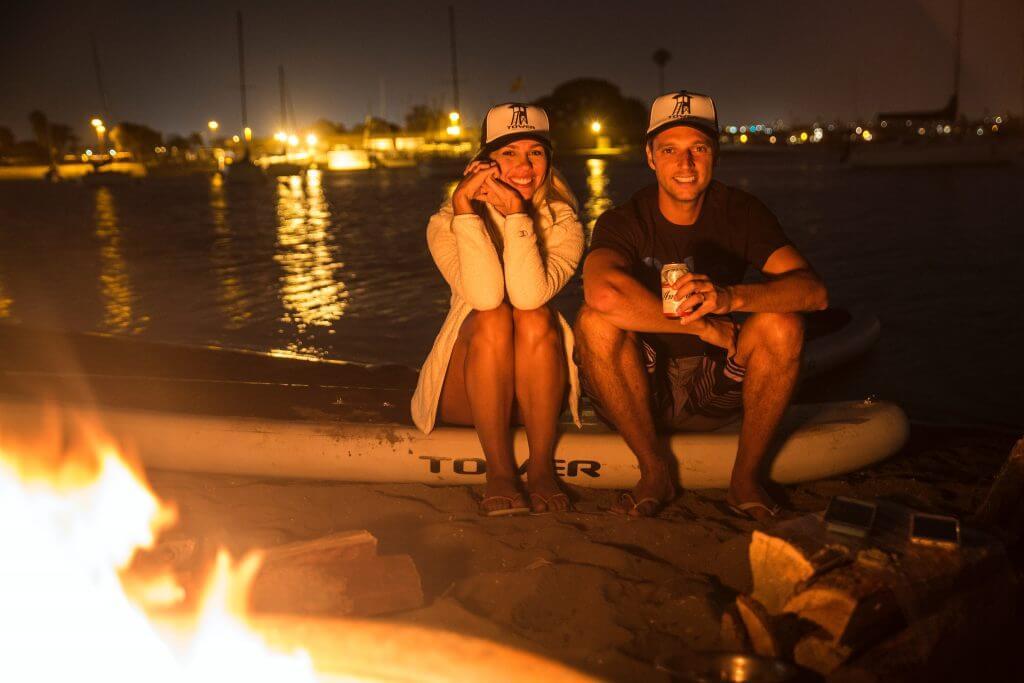 2 person paddle board near campfire