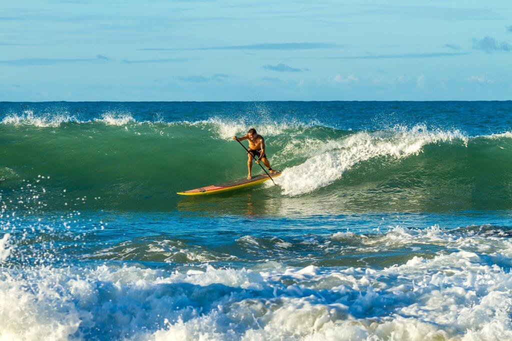 man on surfing sup board on a wave