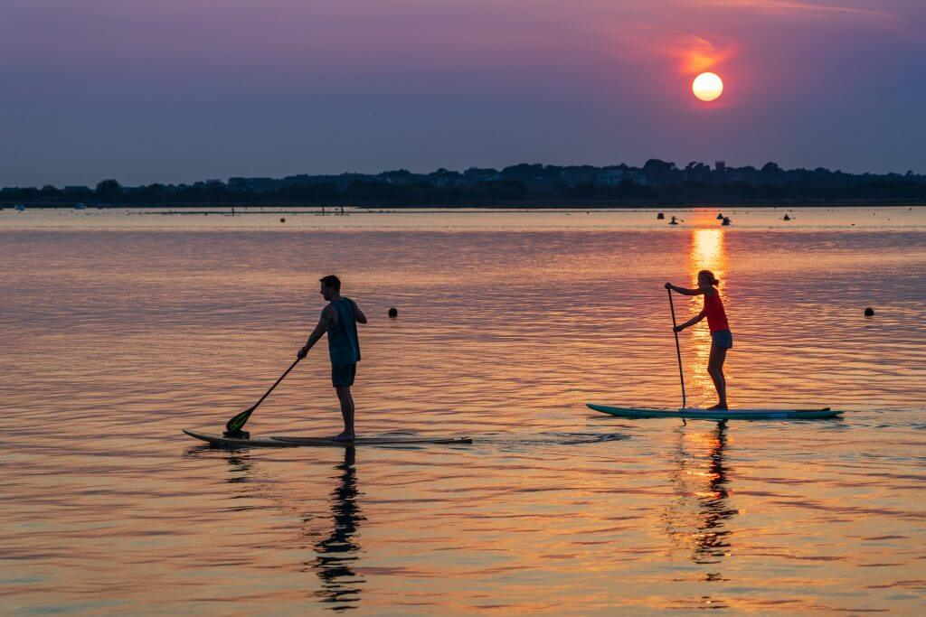 Two people paddling at sunset