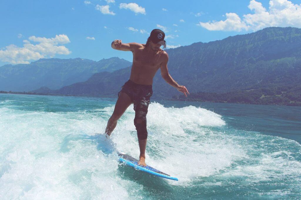 man wakesurfing with hat on