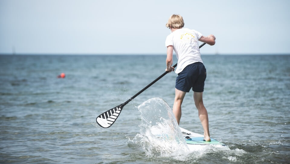 kid paddling on an inexpensive stand up sup