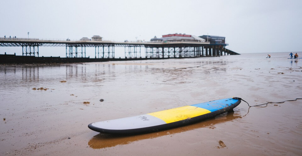 epoxy sup on the beach with pier in the background