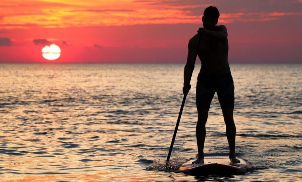 Man paddling on the ocean at sunset