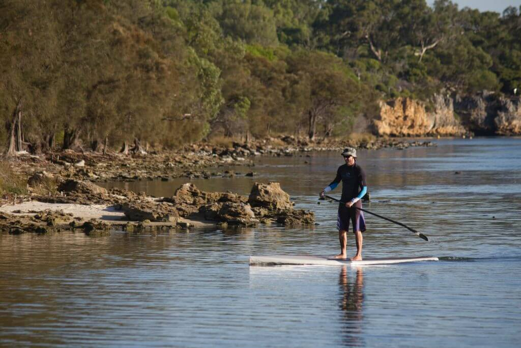 man paddling on a rigid stand up sup near a rocky shore