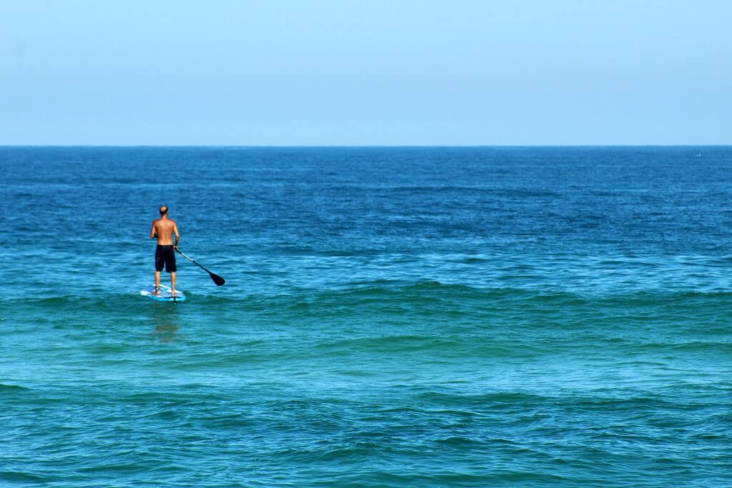 man on the water paddling a solid sup