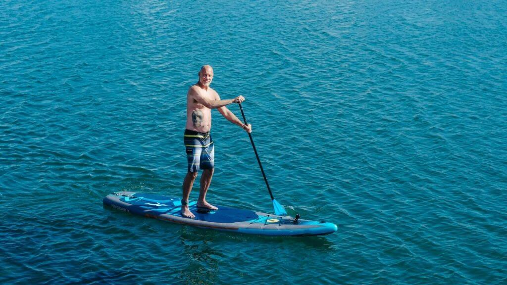 heavy old guy paddling on a SUP